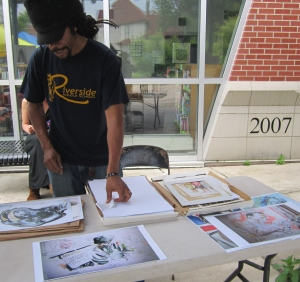 Hollowell's brother, Freeze, arranges prints for sale at the Southeast Area Farmers' Market Summer Celebration.
